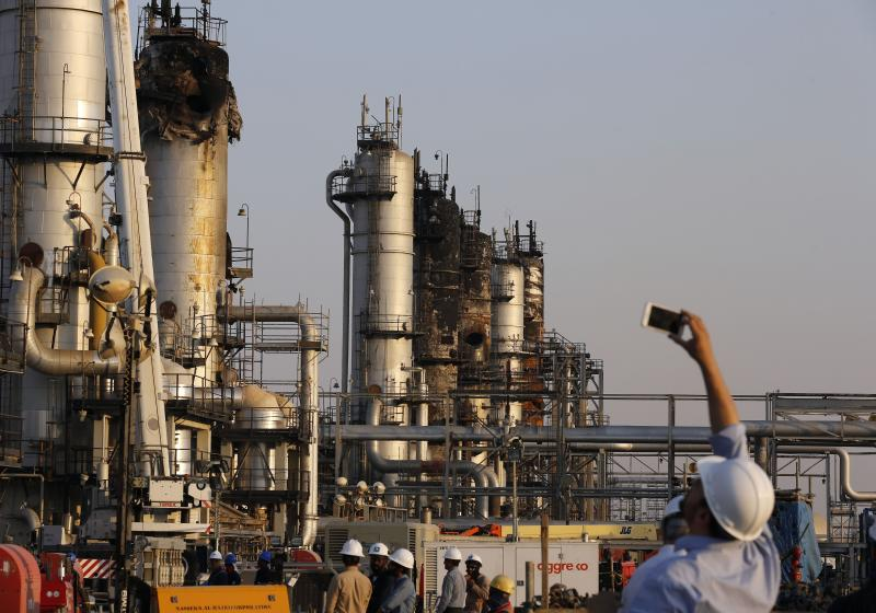 """FILE- In this Friday, Sept. 20, 2019, file photo, during a trip organized by Saudi information ministry, a cameraman films Aramco's oil processing facility after the recent Sept. 14 attack in Abqaiq, near Dammam in the Kingdom's Eastern Province. Saudi Arabian oil company Aramco's initial public offering raised $29.4 billion, more than previously announced after the company said Sunday it used a so-called """"greenshoe option"""" to sell an additional 450 million shares to satiate investor demand. (AP Photo/Amr Nabil, File)"""