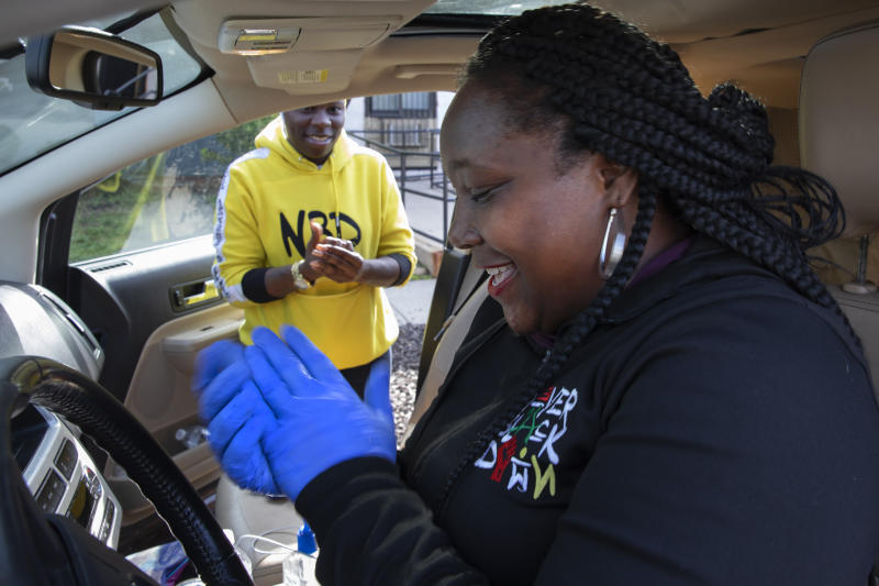 In this March 29, 2020, photo, volunteers Regina Summers, left, and Tonisha Wallace, use hand sanitizer between donated food deliveries in southeast Washington. Neighborhood deliveries are part of a new Martha's Table initiative, along with community partners, to get needed food directly to the neighborhoods they serve. These local volunteers are the tip of the spear for a grassroots community effort to keep Washington's most vulnerable neighborhoods fed during the unprecedented coronavirus crisis which has nearly shut down the American economy. (AP Photo/Jacquelyn Martin)