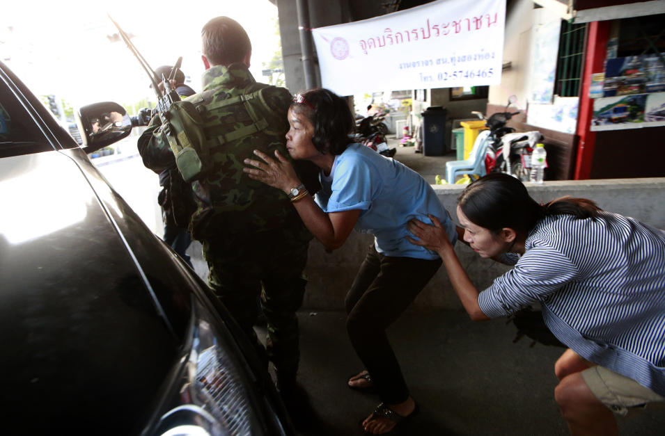 Residents take cover behind Thai soldiers who were sent in to rescue people following clashes between anti and pro-government groups in Bangkok, Thailand, Saturday, Feb. 1, 2014. Gunfire rang out at a major intersection in Thailand's capital on Saturday as clashes between protesters and government supporters erupted on the eve of tense nationwide elections. At least seven people are reported wounded, including an American photojournalist.(AP Photo/Wason Wanichakorn)