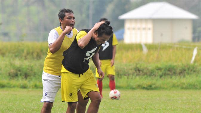 Asisten pelatih Arema FC, Kuncoro (kiri) sedang bercanda dengan Hanif Sjahbandi saat latihan. (Bola.com/Iwan Setiawan)