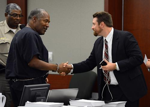O.J. Simpson shakes hands with defense team member Josh Barry at the end of an evidentiary hearing in Clark County District Court on Friday, May 17, 2013 in Las Vegas. Simpson, who is currently serving a nine-to-33-year sentence in state prison as a result of his October 2008 conviction for armed robbery and kidnapping charges, is using a writ of habeas corpus to seek a new trial, claiming he had such bad representation that his conviction should be reversed. (AP Photo/Ethan Miller, Pool)