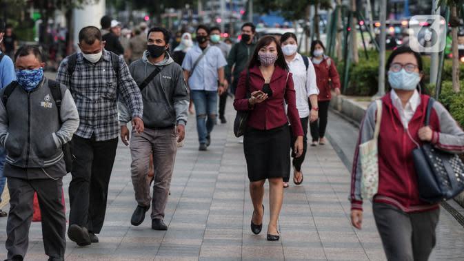 Sejumlah orang berjalan di trotoar pada saat jam pulang kantor di Kawasan Sudirman, Jakarta, Senin (8/6/2020). Aktivitas perkantoran dimulai kembali pada pekan kedua penerapan Pembatasan Sosial Berskala Besar (PSBB) transisi pandemi COVID-19. (Liputan6.com/Johan Tallo)