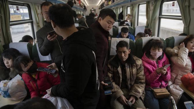 Penumpang menaiki kereta api menuju kota asal mereka di Beijing, Selasa (29/1). Jutaan orang China telah memulai migrasi manusia terbesar di dunia meninggalkan kota-kota besar menuju kampung halaman untuk merayakan Tahun Baru Imlek. (Nicolas ASFOURI/AFP)