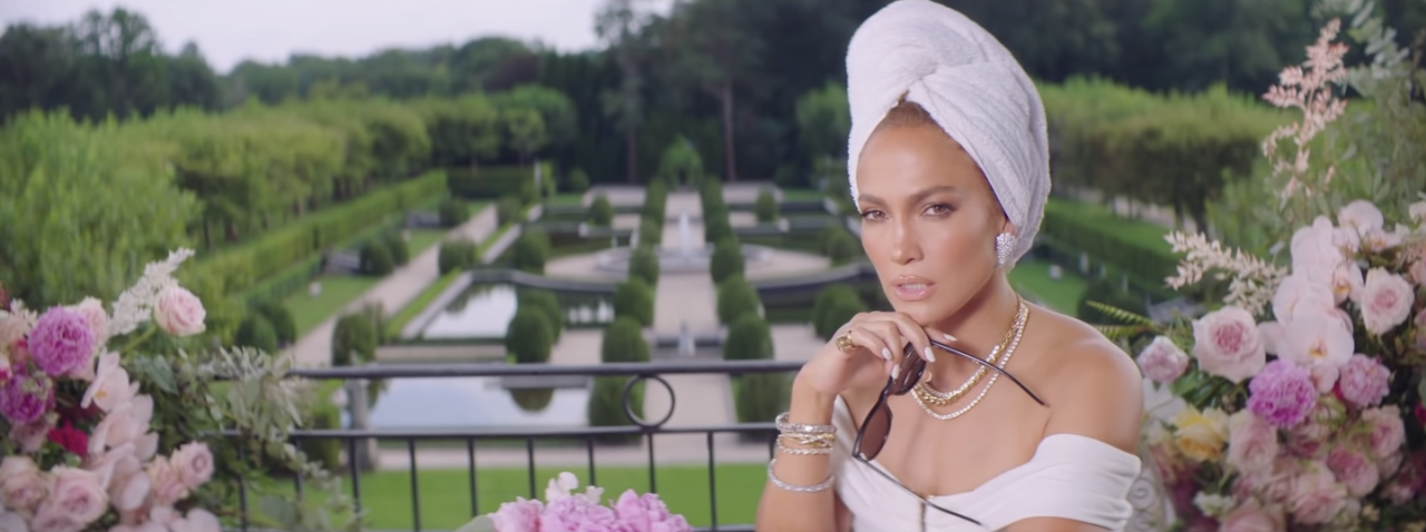 <p>The music video begins with J.Lo sitting on a terrace overlooking a garden. With her hair wrapped up in a white towel, she wears diamond necklaces and bracelets, and a white off-the-shoulder top.</p>