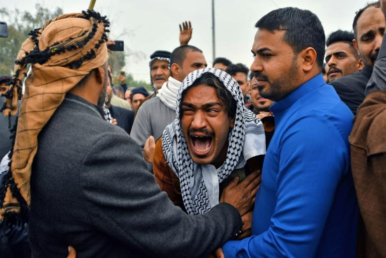 An Iraqi man mourns his brother during a funeral procession for anti-government demonstrators killed during protests a day earlier, in the shrine city of Najaf
