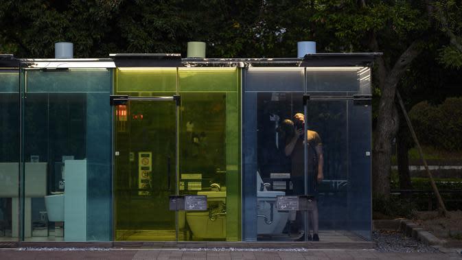 Seorang pria menggunakan toilet transparan di Haru-no-Ogawa Community Park di distrik Shibuya, Tokyo (19/8/2020). Toilet ini dirancang oleh arsitek Shigeru Ban dimana dinding luar kacanya akan berubah menjadi buram ketika kuncinya ditutup. (AFP Photo/Philip Fong)