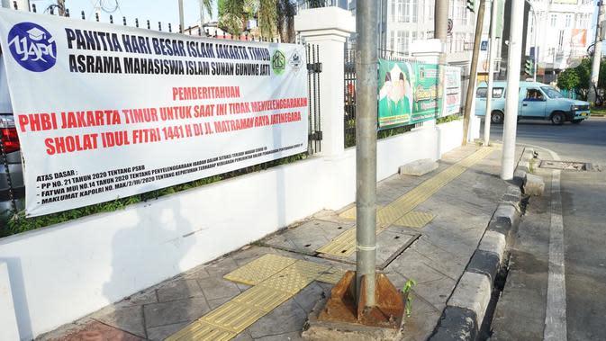 Spanduk pemberitahuan peniadaan salat id terpasang di Jalan Matraman Raya, Jakarta, Minggu (24/5/2020). Adanya pandemi Covid-19 menyebabkan kegiatan salat id 1441 H di lokasi tersebut ditiadakan. (Liputan6.com/Immanuel Antonius)