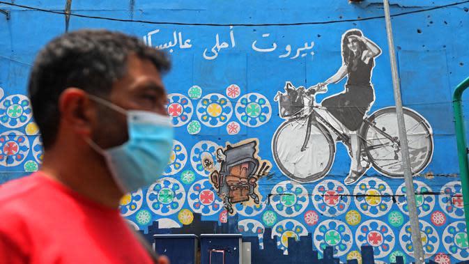 Seorang pria berjalan melewati sebuah grafiti yang mendorong kegiatan bersepeda di Beirut, Lebanon (11/6/2020). Belakangan ini, kegiatan bersepeda menjadi aktivitas yang lazim di Lebanon sejak pemerintah memberlakukan pembatasan guna meredam pandemi COVID-19. (Xinhua/Bilal Jawich)