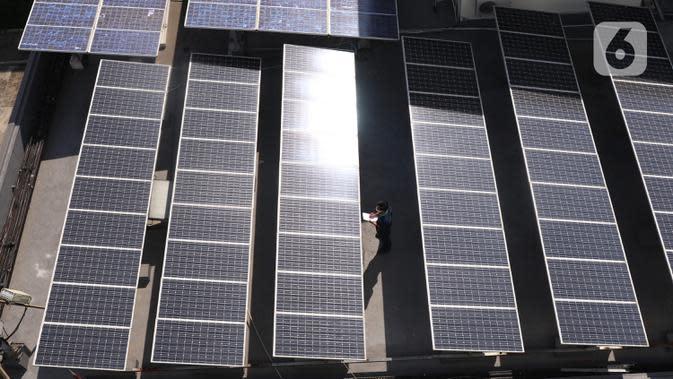 Pekerja melakukan pengecekan panel surya di atas gedung di kawasan Jakarta, Senin (31/8/2020). Pemerintah tengah menyiapkan peraturan presiden terkait energi baru terbarukan dan konservasi energi agar target 23 persen bauran energi di Indonesia bisa tercapai pada 2045. (Liputan6.com/Angga Yuniar)