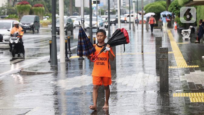 Seorang anak menawarkan jasa ojek payung di tengah hujan yang turun di kawasan Bundaran HI, Jakarta, Senin (3/2/2020). Hujan deras yang mengguyur sejumlah wilayah di DKI Jakarta dimanfaatkan para pengojek payung untuk mencari penghasilan tambahan. (Liputan6.com/Angga Yuniar)