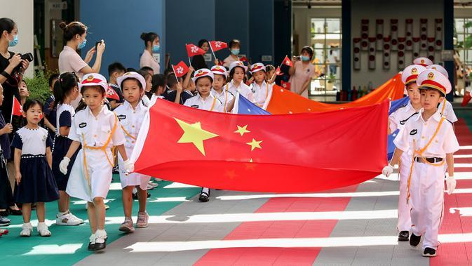 Anak-anak memegang bendera China saat upacara pengibaran bendera di sebuah taman kanak-kanak di Shenzhen, Provinsi Guangdong, China, Selasa (30/6/2020). Hong Kong menandai 23 tahun penyerahan dari Inggris ke Cina pada 1 Juli. (STR/AFP)