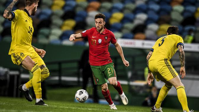 Penyerang Portugal, Diogo Jota, berebut bola dengan gelandang Swedia, Victor Lindelof, pada laga UEFA Nations League 2020/2021 di Estadio Jose Alvalade, Kamis (15/10/2020) dini hari WIB. Portugal menang 3-0 atas Swedia. (AFP/Patricia De Melo Moreira)