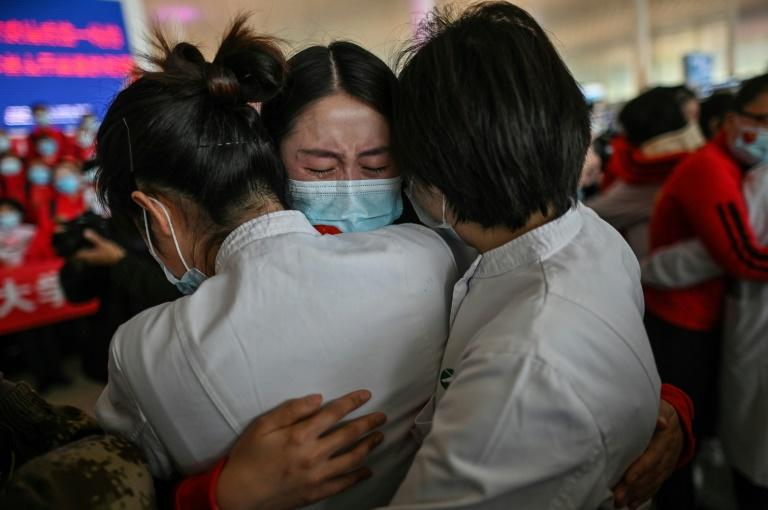 A medical worker leaving Wuhan hugs colleagues before boarding a plane back home
