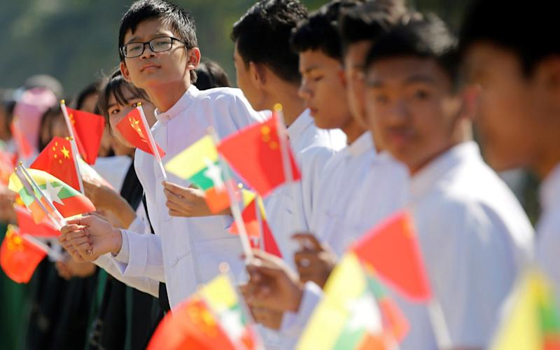 Myanmar students hold Myanmar and Chinese flags as they prepare to welcome Chinese President Xi Jinping outside of the airport in Naypyitaw - REUTERS