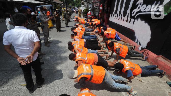 Puluhan pelanggar PSBB diberi hukuman push-up saat razia masker di Pasar Reni, Pamulang, Tangerang Selatan, Banten, Selasa (1/9/2020). Razia terhadap pedagang dan pengunjung pasar ini juga dilakukan rapid test guna mencegah penularan COVID-19. (merdeka.com/Arie Basuki)
