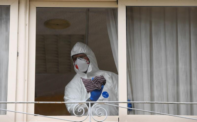 FILE PHOTO: FILE PHOTO: A sanitary worker cleans the nursing home where a woman died and several residents and care providers have been diagnosed with coronavirus disease (COVID-19) in Grado