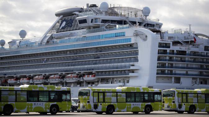 Bus-bus terparkir dekat kapal pesiar Diamond Princess yang dikarantina di sebuah pelabuhan di Yokohama, Jepang, Rabu (19/2/2020). Kedutaan Besar Republik Indonesia di Tokyo mengonfirmasi WNI yang terinfeksi virus corona (COVID-19) di kapal itu bertambah menjadi empat orang. (AP Photo/Jae C. Hong)