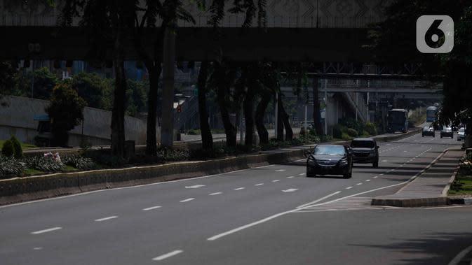Sejumlah kendaraan melintas di ruas jalan protokol di Jakarta, Jumat (10/4/2020). Pemerintah resmi memberlakukan PSBB setelah adanya Peraturan Pemerintah (PP) Nomor 21 Tahun 2020 dengan didukung oleh Peraturan Menteri Kesehatan (PMK) Nomor 9 Tahun 2020. (Liputan6.com/Angga Yuniar)