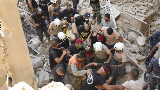 Tim penyelamat membawa korban selamat yang dikeluarkan dari puing-puing setelah ledakan besar di Beirut, Lebanon, Rabu (5/8/2020). Ledakan yang mengakibatkan puluhan orang tewas dan ribuan lainnya terluka tersebut meratakan pelabuhan dan merusak bangunan di seluruh Beirut. (AP Photo/Hassan Ammar)