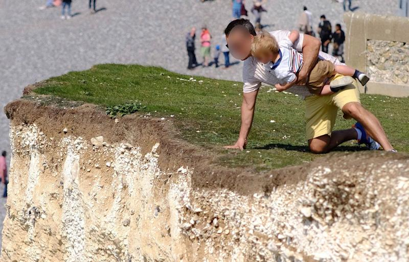 A father clutches his toddler uncomfortably close to the edge of the Seven Sisters cliffs in East Sussex, England. Source: Australscope