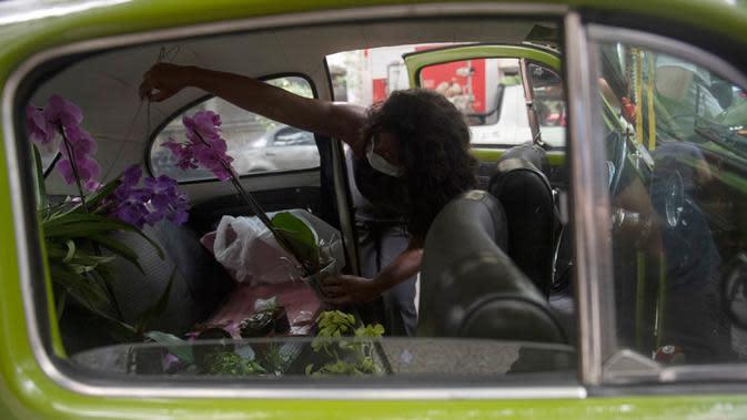 Roberta Machado dari Brasil menata bunga dan tanaman untuk dijual dengan Volkswagen Beetle 1969 yang diubah menjadi toko bunga keliling di Copacabana, Rio de Janeiro, Rabu (14/10/2020). Perempuan 51 tahun ini mengubah VW kodok untuk bertahan dari krisis akibat pandemi COVID-19. (MAURO PIMENTEL/AFP)