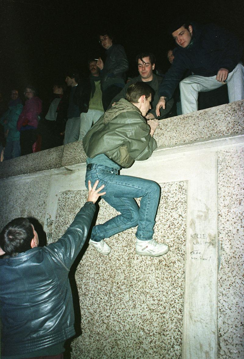 East German citizens help each other climb the Berlin Wall at the Brandenburg gate after the opening of East German borders in this early Nov. 10, 1989. (Photo: Reuters)