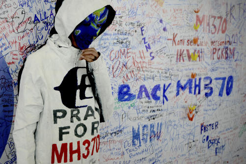 "CORRECTS THAT WOMAN IS WEARING A MASK INSTEAD OF FACE PAINT - An unidentified woman wearing a mask depicting the flight of the missing Malaysia Airline, MH370, poses in front of the ""wall of hope"" at Kuala Lumpur International Airport in Sepang, Malaysia, Monday, March 17, 2014. The search for the missing Malaysian jet pushed deep into the northern and southern hemispheres Monday as Australia scoured the southern Indian Ocean and China offered 21 satellites to respond to Malaysia's call for help in the unprecedented hunt. (AP Photo/Joshua Paul)"