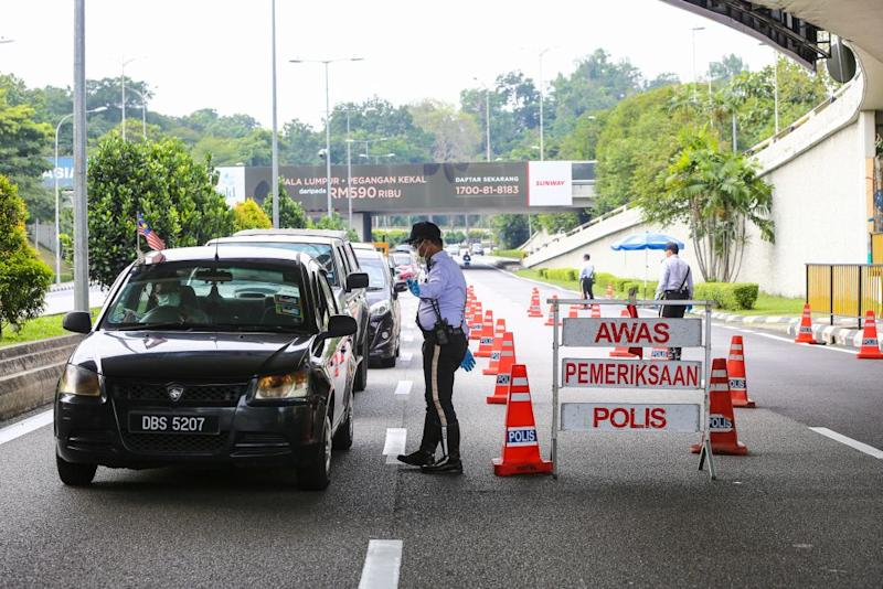 A traffic policeman conducts checks on vehicles during a roadblock on Jalan Sultan Ismail in Kuala Lumpur October 14, 2020. Employees are currently allowed to move about for work purposes and to go to their offices under the conditional movement control order (CMCO), said senior minister Datuk Seri Ismail Sabri Yaakob today. — Picture by Yusof Mat Isa