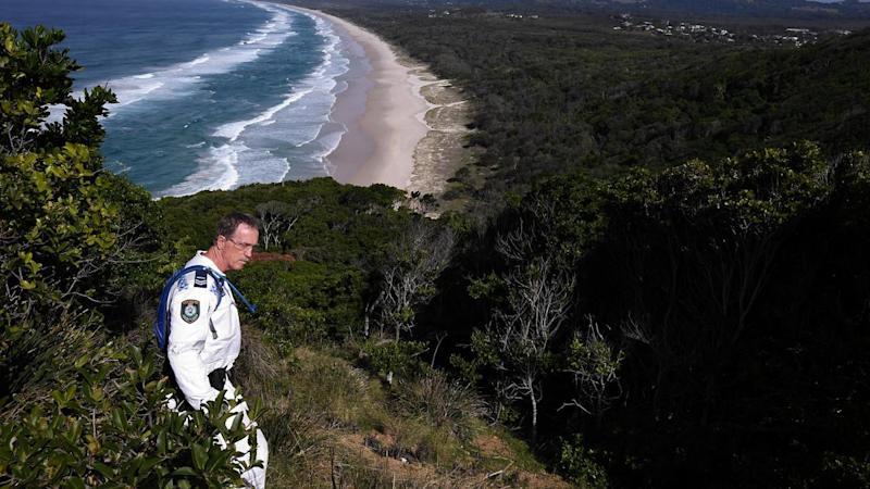 A police officer searches in bush scrub near a beach.