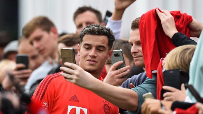 Gelandang baru Bayern Munchen, Philippe Coutinho berselfie dengan fans saat mengikuti sesi pelatihan di Munich, Jerman selatan (20/8/2019). Munchen meminjam Coutinho dari Barcelona selama satu musim dengan biaya 8,5 juta euro atau sekitar Rp 134,3 miliar. (AFP Photo/Christof Stache)