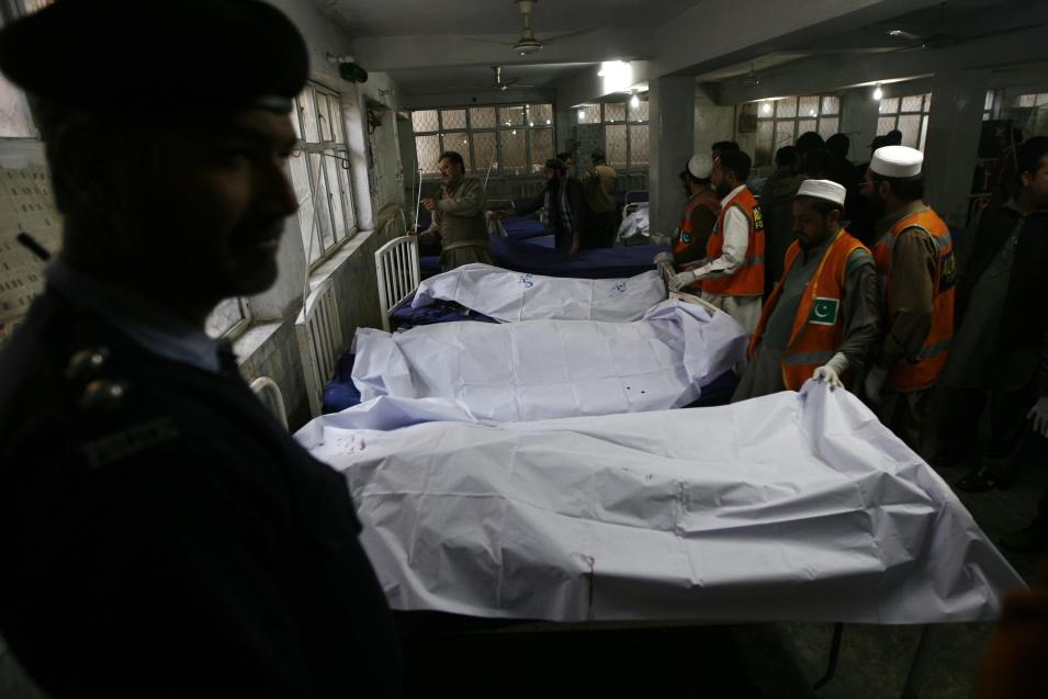 Security officials and rescue workers stand near bodies of victims killed in a grenade attack, at a hospital morgue in Peshawar