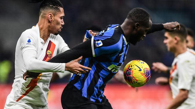 Striker Inter Milan, Romelu Lukaku, berebut bola dengan bek AS Roma, Chris Smalling, pada laga Serie A Italia di Stadion San Siro, Milan, Jumat (6/12). Kedua klub bermain imbang 0-0. (AFP/Miguel Medina)