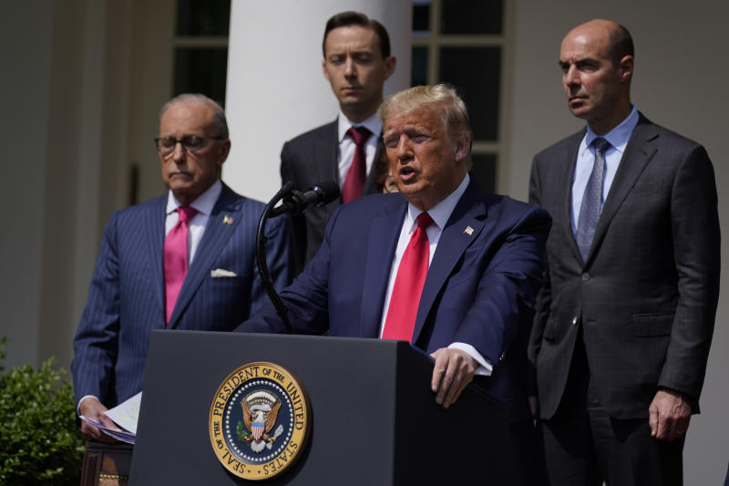President Donald Trump speaks during a news conference in the Rose Garden of the White House, Friday, June 5, 2020, in Washington. White House chief economic adviser Larry Kudlow, left, and Labor Secretary Eugene Scalia, top right listen. (AP Photo/Evan Vucci)