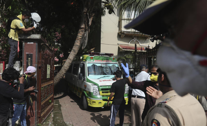 An ambulance carrying the body of Bollywood actor Sushant Singh Rajput leaves from the building he lived in Mumbai, India, Sunday, June 14, 2020. Rajput was found dead at his Mumbai residence on Sunday, police and Indian media reports said. (AP Photo/Rafiq Maqbool)