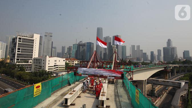 Pekerja melakukan pengecoran tahap akhir jembatan lengkung bentang panjang atau long span pada proyek LRT Jabodebek di kawasan Kuningan, Jakarta, Senin (11/11/2019). Long span tersebut menjadi yang terpanjang di dunia. (Liputan6.com/Angga Yuniar)