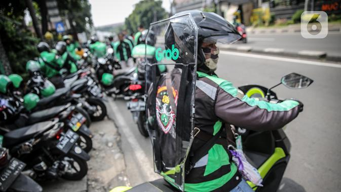 Driver Grab Bike mengenakan Grab Protect pelindung yang membatasi antara pengemudi dan penumpang saat diluncurkan di Jakarta, Selasa (9/6/2020). Penumpang ojek online (ojol) kini tak perlu khawatir menggunakan transportasi ini di tengah pandemi Corona. (Liputan6.com/Faizal Fanani)