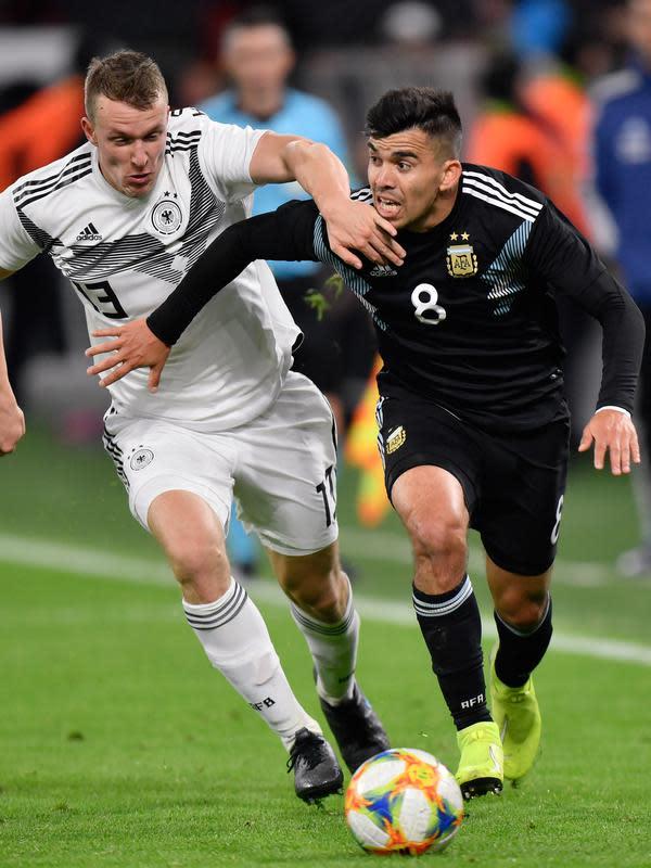 Pemain Timnas Argentina Marcos Acuna berebut bola dengan pemain Timnas Jerman Lukas Klostermann dalam laga persahabatan di Stadion Signal Iduna Park, Dortmund, Rabu (9/10/2019). (AP/Martin Meissner)