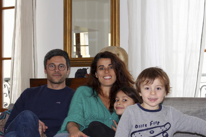 In this photo taken Thursday April 30, 2020 Mathilde Manaud et Kimkhi Nguyen, left, pose on a sofa with their children Mila, 7, and Andre, 3, in Paris. As France prepares to start letting public life resume after eight weeks, many parents are deeply torn over a question without a clear or conclusive answer: Should I send my child back to school?  The French government is easing some of the closure and home-confinement orders it imposed March 17 to curb coronavirus infections, with businesses permitted to reopen, residents cleared to return to workplaces and schools welcoming some students again starting Monday.   (AP Photo/Oleg Cetinic)
