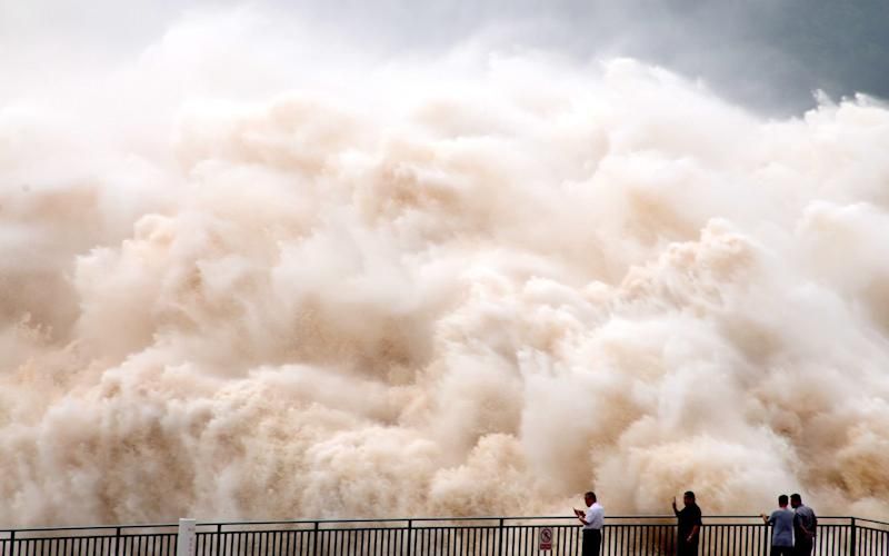 A huge wall of water slams into Jiyuan. The colour combination of yellow and white due to different sand content - SplashNews.com/Splash News