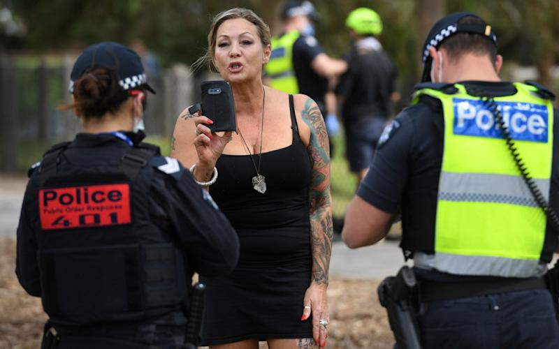 Police detain an anti-lockdown protester in the Melbourne suburb of Elsternwick - AFP