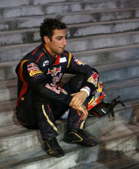 Toro Rosso Formula One driver Ricciardo sits down on steps after crashing during the Singapore F1 Grand Prix in Singapore