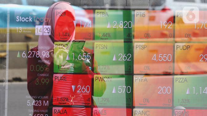 Pejalan kaki melintas dekat layar pergerakan Indeks Harga Saham Gabungan (IHSG) di kawasan Jakarta, Senin (13/1/2020). IHSG menguat 0,34 persen atau 21 poin ke level 6.296 pada penutupan perdagangan Senin (13/1) sore ini. (Liputan6.com/Angga Yuniar)