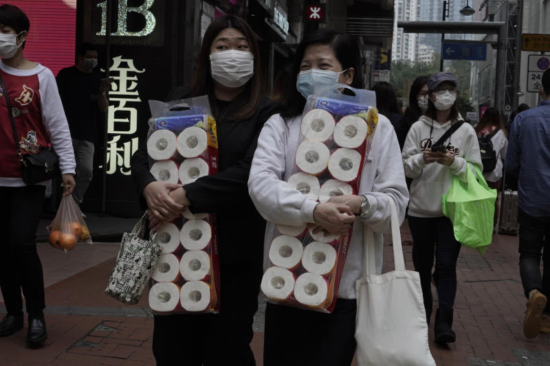 Two women carry supplies of toilet paper at a street in Hong Kong, Friday, Feb. 14, 2020. China on Friday reported another sharp rise in the number of people infected with a new virus, as the death toll neared 1,400. (AP Photo/Kin Cheung)