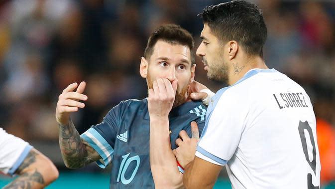 Megabintang timnas Argentina, Lionel Messi berbicara dengan pemain timnas Uruguay, Luis Suarez pada laga persahabatan di Stadion Bloomfield, Tel Aviv, Senin (18/11/2019). Messi dan Cavani bersitegang sehingga keduanya harus sampai dipisahkan rekan-rekannya. (AP/Ariel Schalit)