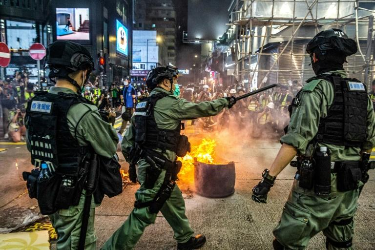 Police stand guard to deter pro-democracy protesters from blocking roads in the Mong Kok district of Hong Kong on May 27, 2020