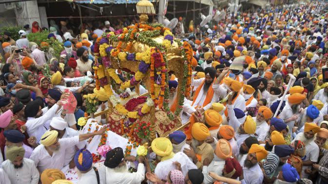 Umat Sikh membawa teks pokok agama Sikhisme, Palki Guru Granth Sahib selama prosesi keagamaan dari Gurudwara Ramsar ke Akal Takht Sahib di Kuil Emas, Amritsar, India, Rabu (19/8/2020). Acara ini untuk memperingati 416 tahun pelantikan Guru Granth Sahib. (NARINDER NANU/AFP)