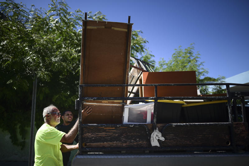 Relatives of 27-year-old Alexandra Colberg move furniture from her earthquake-damaged home in Guanica, Puerto Rico, Tuesday, Jan. 7, 2020. A 6.4-magnitude earthquake struck Puerto Rico before dawn on Tuesday, killing one man, injuring others and collapsing buildings in the southern part of the island. (AP Photo/Carlos Giusti)