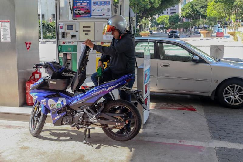 A man refuels his motorcycle at a petrol station in Kuala Lumpur as the movement control order kicks in on March 18, 2020. — Picture by Firdaus Latif