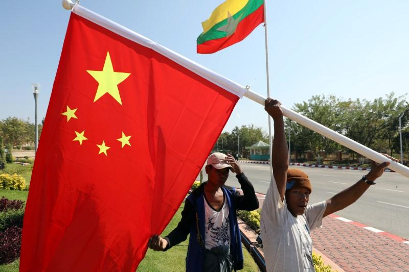 Workers put up flags a day before Chinese President Xi Jinping's visit to Myanmar in Naypyitaw