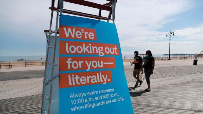 Sejumlah orang melewati papan pemberitahuan jam berenang di sebuah pantai di Coney Island, New York City, 1 Juli 2020. Pada Rabu (1/7), delapan pantai di New York City secara resmi dibuka untuk berenang selama jam kerja harian penjaga pantai, yakni mulai pukul 10.00 hingga 18.00. (Xinhua/Wang Ying)